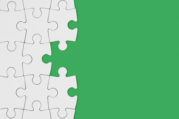 puzzle on green - puzzleteile stock-fotos und bilder