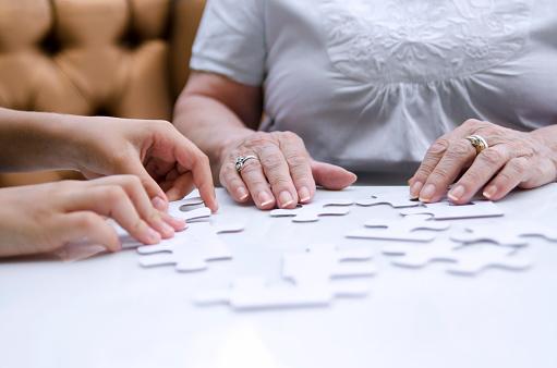 istock Puzzle piece in senior woman hands. 1162598317