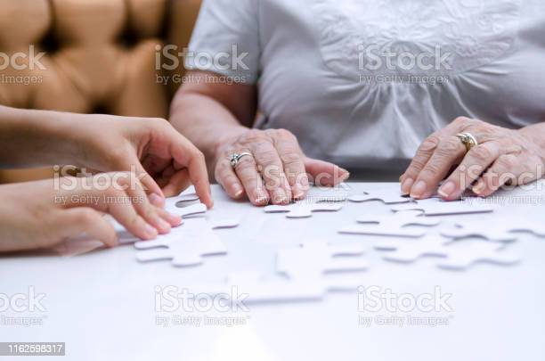 Puzzle piece in senior woman hands picture id1162598317?b=1&k=6&m=1162598317&s=612x612&h=ap8tyjp462ube9ub1hp9i2erxgl9iaz4p9bhgczgqoi=