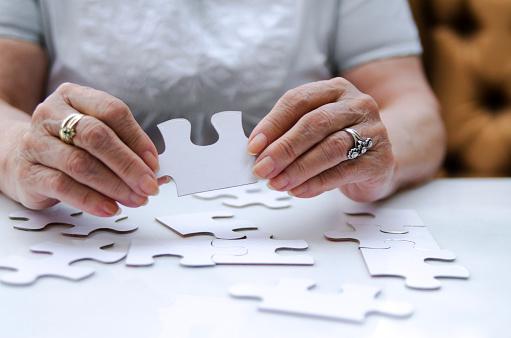 istock Puzzle piece in senior woman hands. 1162598405