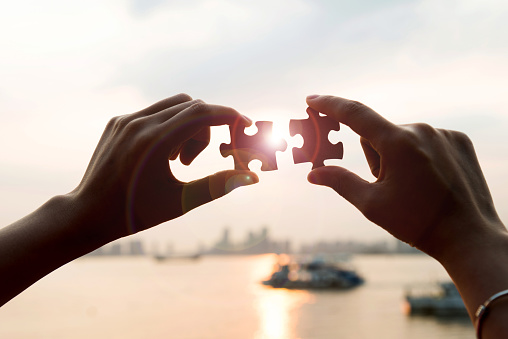 Puzzle pieces and human hands