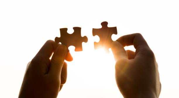 puzzle teile und menschliche hände - twilight teile stock-fotos und bilder