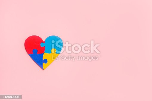 istock Puzzle pieces in form of heart, isolated on pink background. World Autism Awareness Day Concept 1189809061