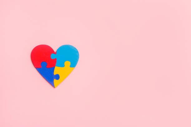 puzzleteile in form von herz, isoliert auf rosa hintergrund. konzept des welt-autismus-bewusstseinstages - autismus stock-fotos und bilder
