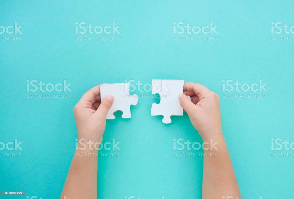 Puzzle pieces on blue background. Autism awareness day. stock photo