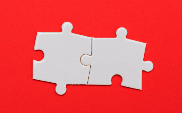 Puzzle pieces on red background, two, close up. Puzzle pieces on red puzzle pieces stock pictures, royalty-free photos & images