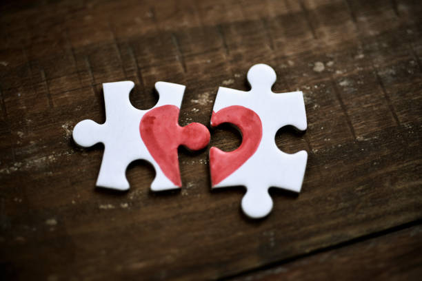 puzzle pieces which form a heart - separation stock photos and pictures
