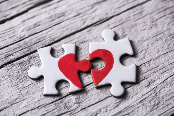 puzzle pieces which form a heart stock photo