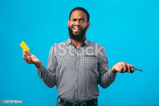 1173546354 istock photo Puzzled afro guy holding credit card and smartphone 1237978344