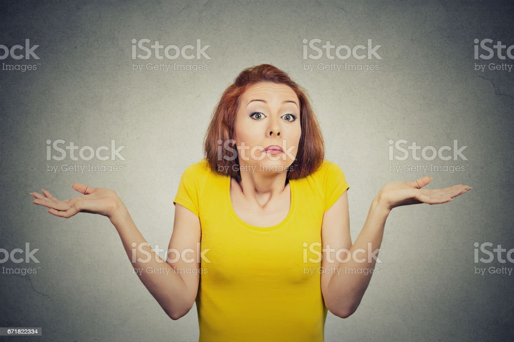 puzzled clueless young woman with arms out asking what is problem who cares so what I don't know stock photo
