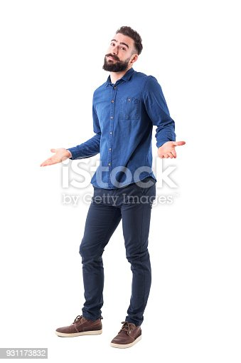 Puzzled confused man in blue shirt shrugging shoulders looking at camera. Full body isolated on white background.