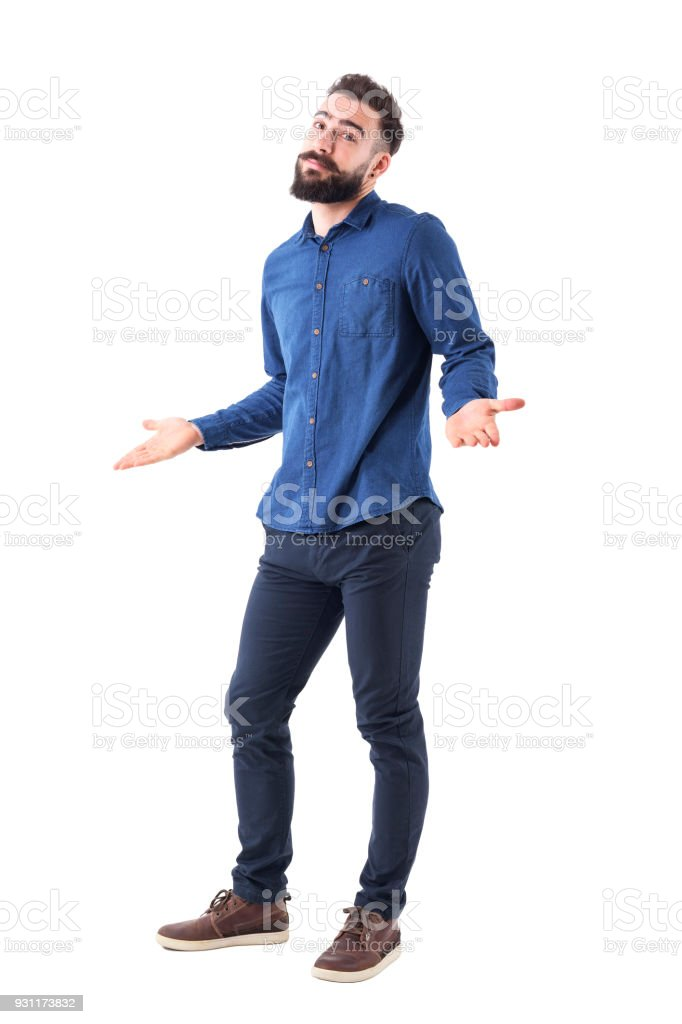 Puzzled confused man in blue shirt shrugging shoulders looking at camera stock photo