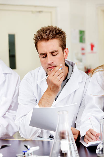 Puzzled lab worker scratches chin stock photo