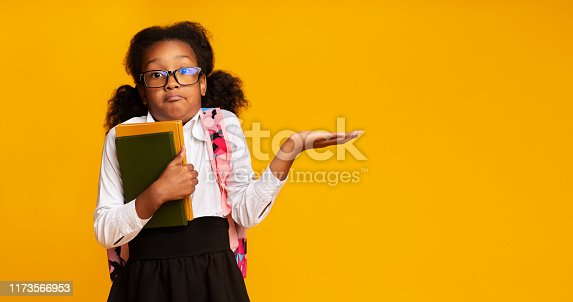 istock Puzzled School Girl Shrugging Shoulders Holding Books On Yellow Background 1173566953