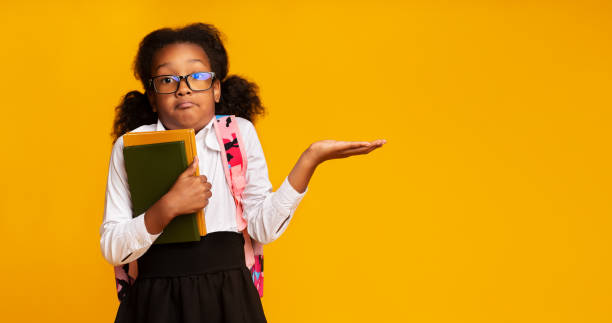 Puzzled School Girl Shrugging Shoulders Holding Books On Yellow Background I Don't Know. Puzzled Black School Girl Shrugging Shoulders Holding Books On Yellow Studio Background. Free Space, Panorama shrugging stock pictures, royalty-free photos & images