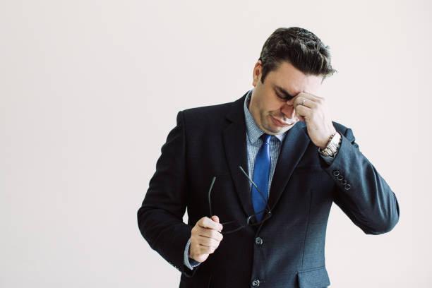 verwirrt müde geschäftsmann reiben nase - migräne vorbeugen stock-fotos und bilder