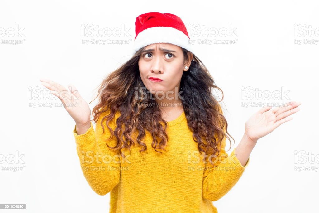 Puzzled woman in santa hat shrugging shoulders royalty-free stock photo