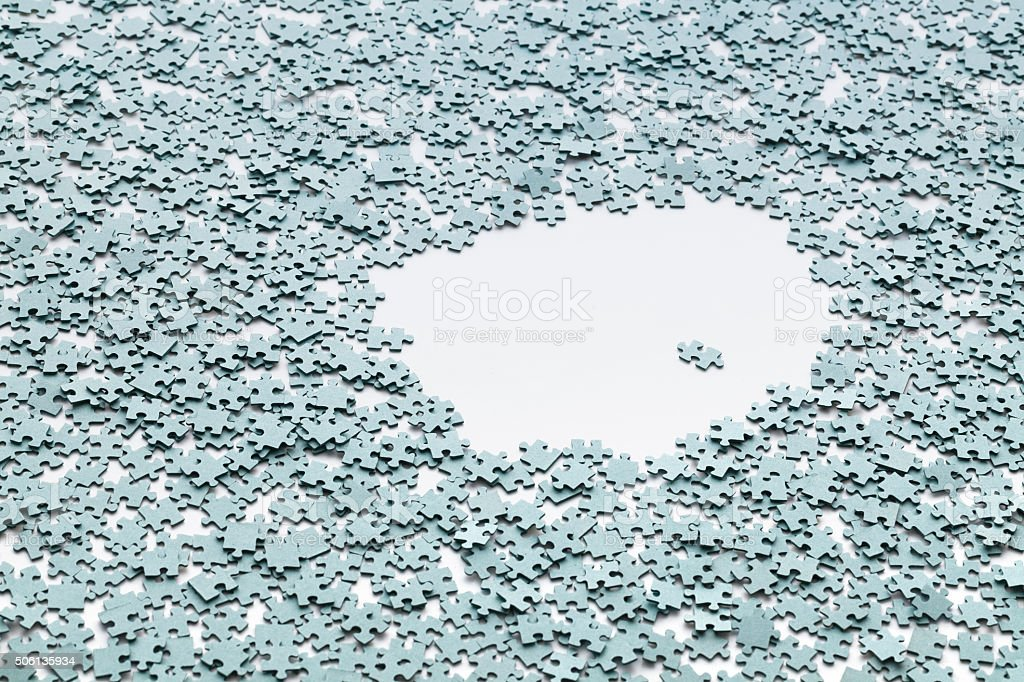 Puzzles on the white background. Lonely in a crowd. stock photo