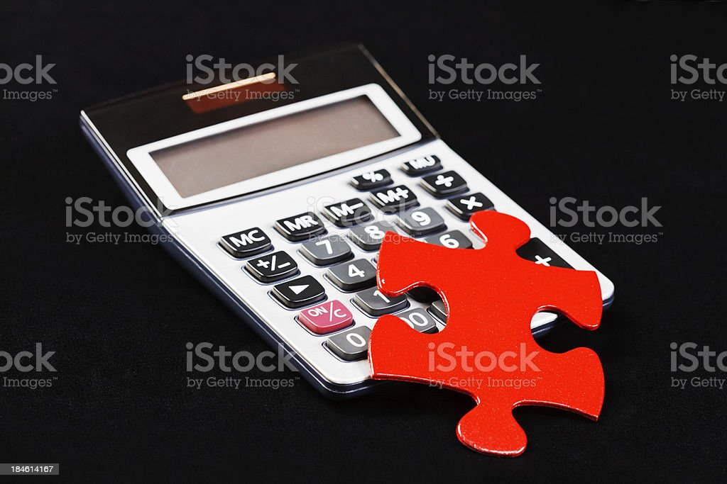 Puzzling calculations; red jigsaw piece on calculator, against black royalty-free stock photo