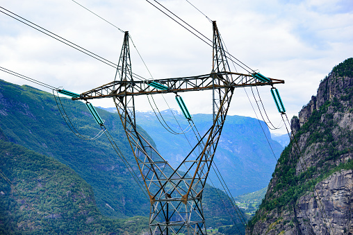 Pylon in mountains, power cables and glaicer in background
