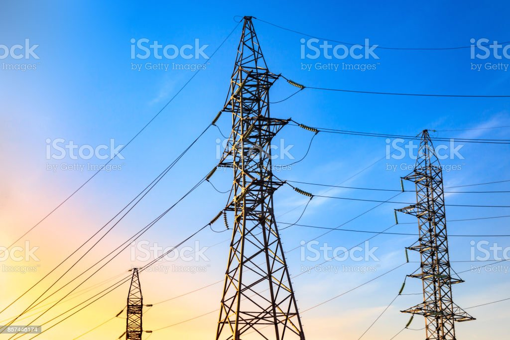 Pylons and transmission power lines on the blue sky background. stock photo