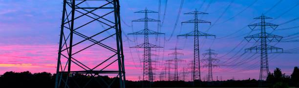 pylons in the evening sun - rete elettrica foto e immagini stock
