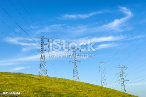 Pylons and power lines on a hillside under a cloudy sky.   Taken in Northern California, USA
