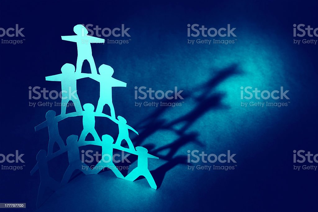 A pyramid of blue paper men on a blue background stock photo