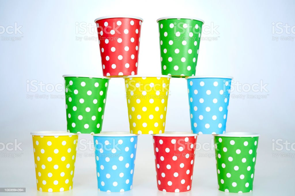 pyramid of multi colored paper cups on white background stock photo