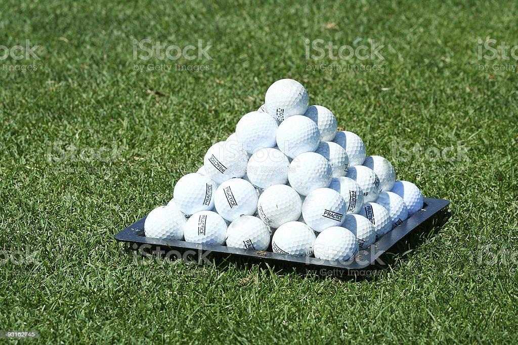 Pyramid of practice golf balls stock photo