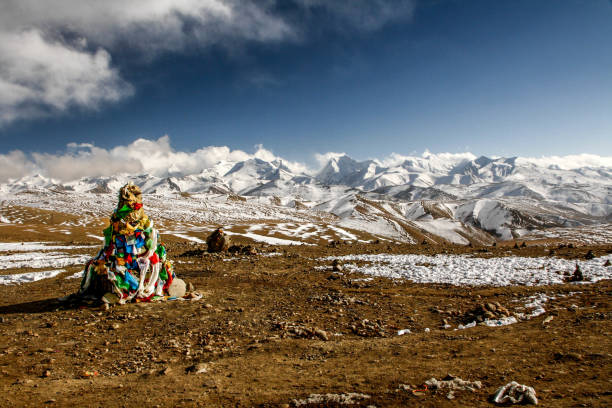 pyramid of prayer flags in front of snow-covered mountains of the himalayas at lalung la pass, 5050m altitude on the friendship highway between lhasa in tibet and kathmandu in nepal - плато стоковые фото и изображения