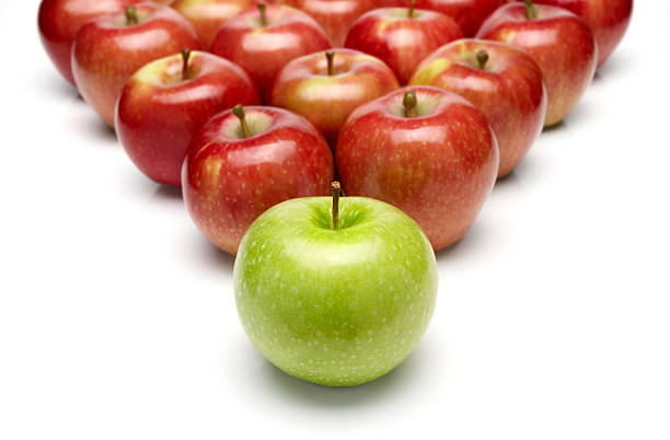 Pyramid of red apples with one green apple in the front stock photo