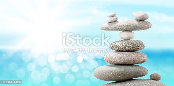 Pyramid of sea pebbles on a sunny beach. Life balance and harmony concept