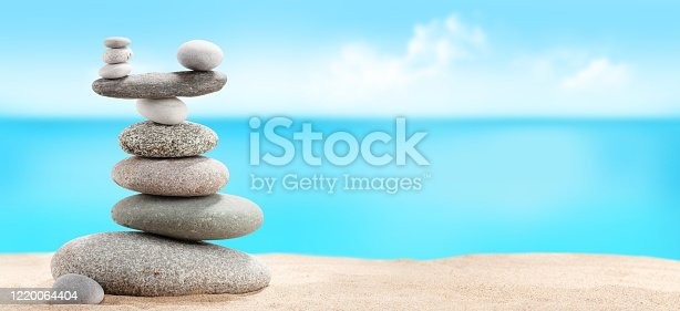 Pyramid of sea pebbles on a sunny sand beach. Life balance and harmony concept