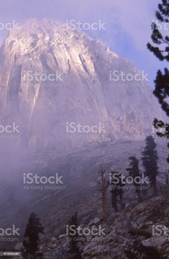 Pyramid Peak rising out of early morning mists in Mineral King Wilderness in Sequoia National Park California stock photo