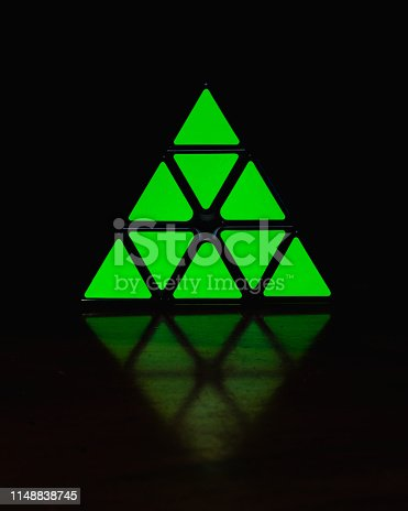 Pyramid puzzle reflecting in the darkness.