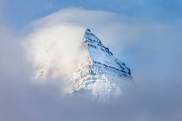 pyramid shaped mount assiniboine in the fog - banff national park stock photos and pictures