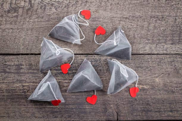 pyramid teebeutel mit bezeichnungsform der herzen auf holztisch hintergrund. valentinstag-konzept. draufsicht mit textfreiraum. - pyramide sammlung stock-fotos und bilder