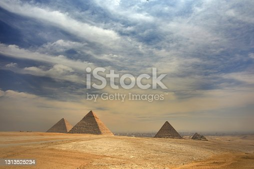 Panoramic view of the pyramids from the Giza Plateau on a sunny day in Cairo, Egypt. From left: the Pyramid of Chufu /Cheops/, Khafre /Chephren/, Menkaure /Mykerinos/ and one of the small pyramids popularly known as Queens' Pyramids. The Pyramid Fields from Giza to Dahshur is on UNESCO World Heritage List