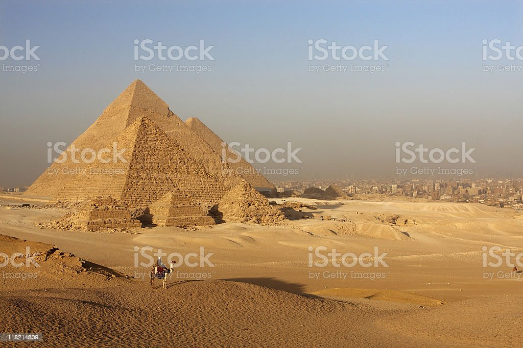 Pyramids in the Egyptian desert, with person riding a camel stock photo