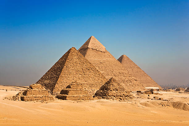 pyramids of giza against blue sky in cairo, egypt - pyramid stock photos and pictures