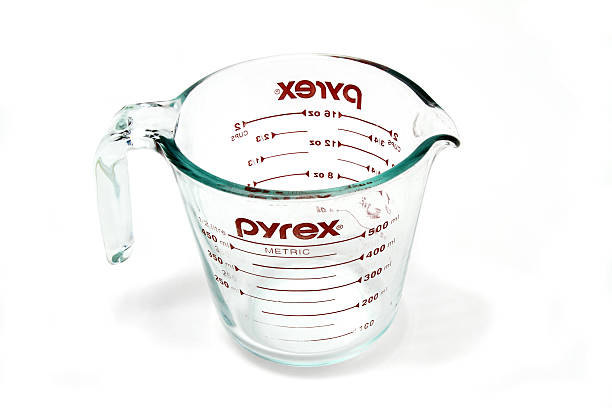 Pyrex glass measuring cup West Palm Beach, USA - May 30, 2015: A PYREX clear glass measuring cup  Pyrex recently celebrated its 100th anniversary since it was introduced by Corning in 1915. The brand is now produced by World Kitchen LLC, a Corning spinoff. dry measure stock pictures, royalty-free photos & images