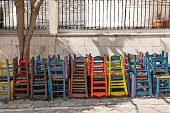 Town square with part of a church (behind the stone wall and metal fence) in the medieval village of Pyrgi on the Greek Island of Chios. In the foreground is a stack of wooden chair painted in different colors. The chairs belong to a traditional taverna with outdoors seating. The village is often referred to as the \