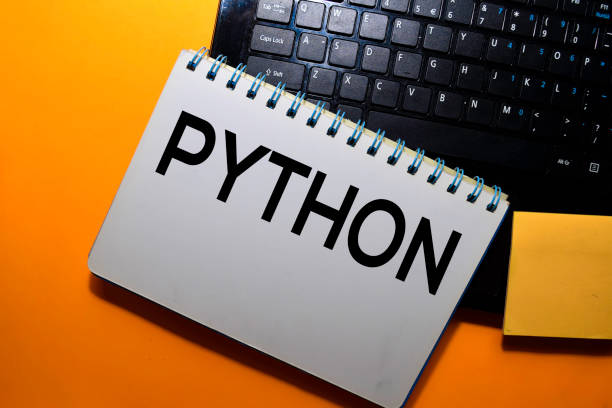 python write on book with laptop keyboard background stock photo