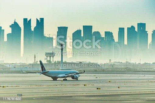 Doha Qatar, Aug 17, 2019: Qatar Airways flight preparing to depart Hamad International Airport with silhouette of city skyline dominating the background