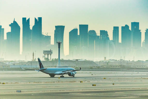 Qatar Airways flight preparing to depart Hamad International Airport with city skyline Doha Qatar, Aug 17, 2019: Qatar Airways flight preparing to depart Hamad International Airport with silhouette of city skyline dominating the background depart stock pictures, royalty-free photos & images