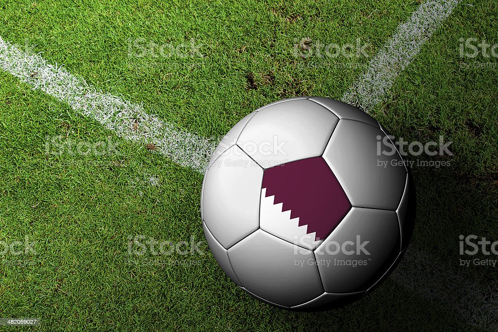 Qatar Flag Pattern of a soccer ball in green grass stock photo