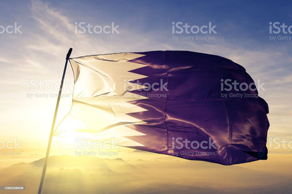 Qatar Qatar bandera paño tela ondeando en la niebla de la niebla de amanecer superior - foto de stock