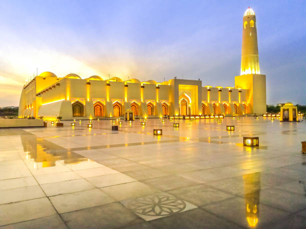 Qatar state mosque Scenic Doha Grand Mosque with minaret illuminated, mirrors on the outdoor marble pavement. Qatar State Mosque, Middle East, Arabian Peninsula in Persian Gulf. Twilight shot. grand mosque stock pictures, royalty-free photos & images