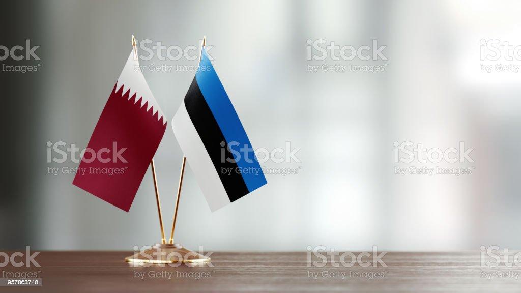 Par de bandera qatarí y Estonia en un escritorio sobre fondo Defocused - foto de stock
